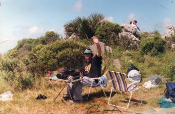 Un radioaficionado en lo que parece un cerro saluda retratado en una foto que parece de los 90.